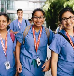 A group of Stanford Medical Youth Science Participants wear scrubs as they walk through the Stanford School of Medicine campus.