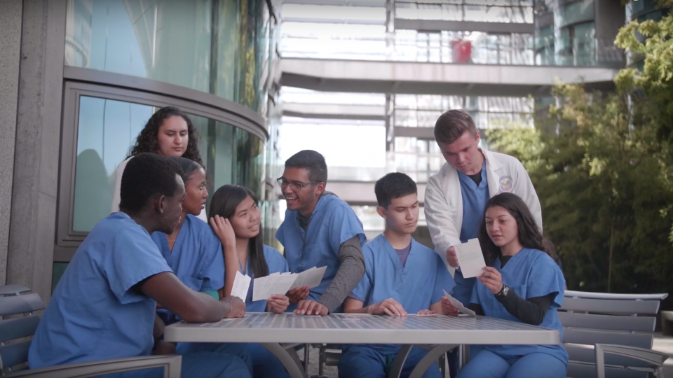 A group of students sits in the Stanford Medical Campus.